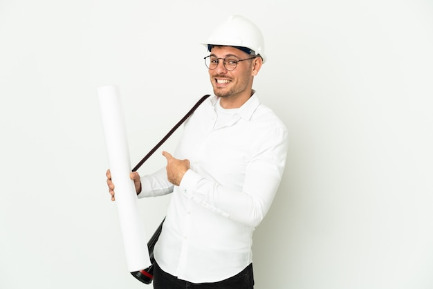 Young architect man with helmet and holding blueprints isolated on white wall pointing back