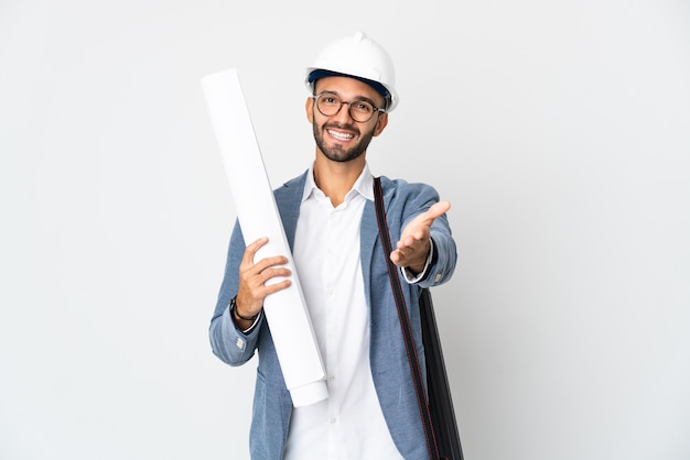 Young architect man with helmet and holding blueprints isolated on white wall shaking hands for closing a good deal