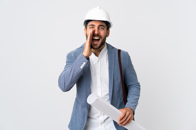 Young architect man with helmet and holding blueprints isolated on white wall shouting with mouth wide open