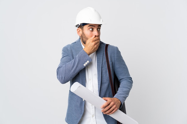 Young architect man with helmet and holding blueprints on white wall covering mouth and looking to the side