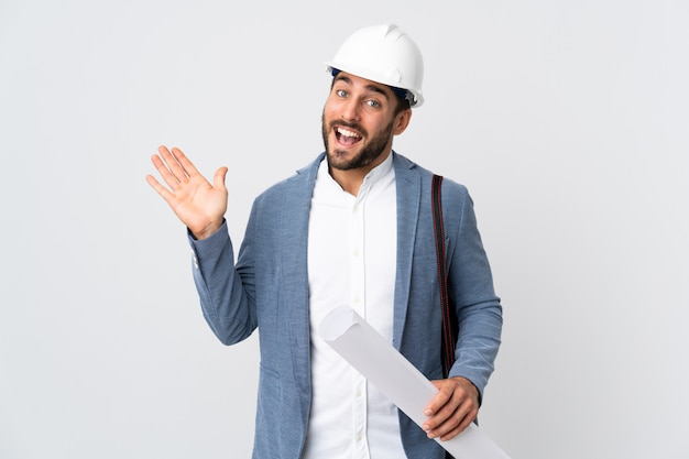 Young architect man with helmet and holding blueprints on white wall saluting with hand with happy expression