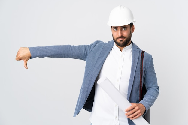 Young architect man with helmet and holding blueprints on white wall showing thumb down with negative expression