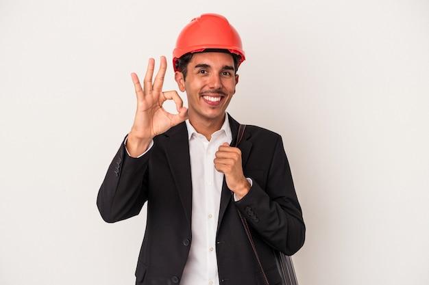若い建築家の混血の男は、白い背景に孤立し、陽気で自信を持って大丈夫なジェスチャーを示しています。