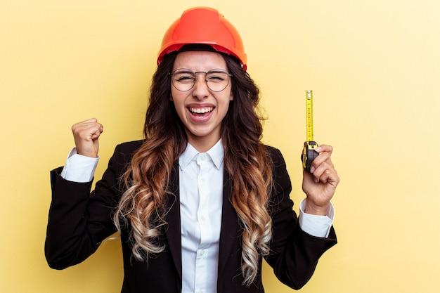 黄色の背景で隔離の測定テープを保持している若い建築家混血の女性