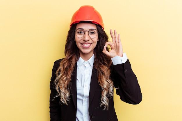 若い建築家の混血の女性は、黄色の背景に孤立し、陽気で自信を持って大丈夫なジェスチャーを示しています。