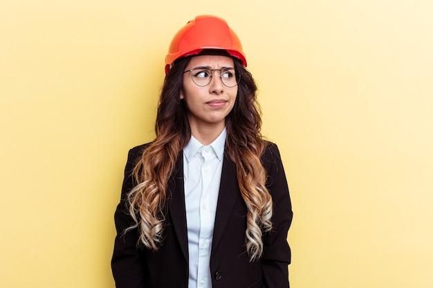黄色の背景に孤立した若い建築家混血の女性は混乱し、疑わしく、不安を感じています。