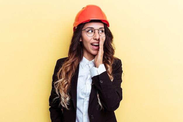 黄色の背景に分離された若い建築家混血の女性は、秘密のホットブレーキのニュースを言って脇を見ています