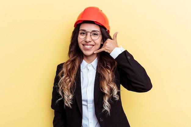 指で携帯電話の呼び出しジェスチャーを示す黄色の背景に分離された若い建築家混血の女性。