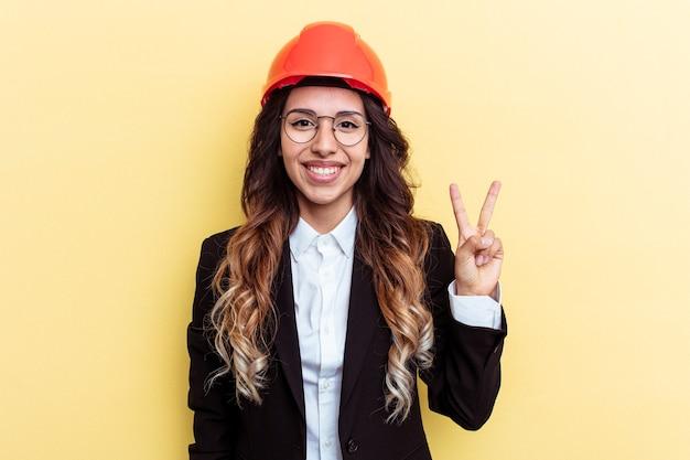 指で2番目を示す黄色の背景に分離された若い建築家混血の女性。