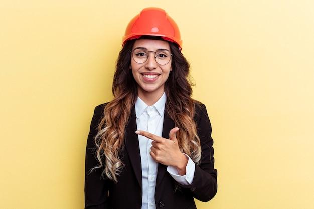 若い建築家混血の女性は、黄色の背景に笑みを浮かべて脇を指して、空白のスペースで何かを示しています。