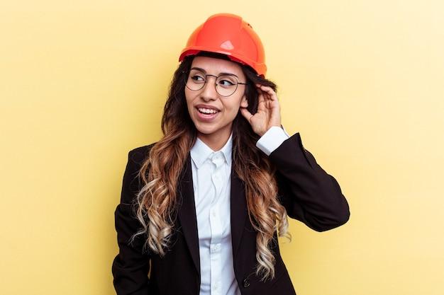 ゴシップを聴こうとしている黄色の背景に分離された若い建築家混血の女性。