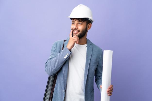 헬멧과 고립 된 청사진을 들고 젊은 건축가 모로코 남자