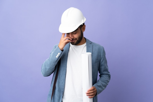 Молодой архитектор марокканский мужчина в шлеме и держит чертежи на изолированном фоне, смеясь