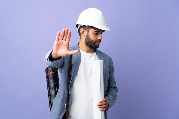 Молодой архитектор марокканский мужчина в шлеме и держит чертежи на изолированном фоне, делая жест стоп и разочарованный