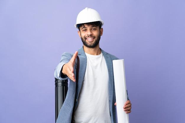 Молодой архитектор марокканский мужчина в шлеме и держит чертежи на изолированном фоне, пожимая руку для заключения хорошей сделки