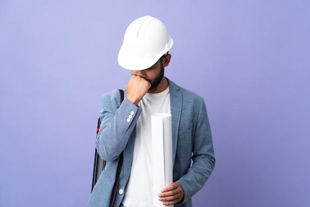 Молодой архитектор марокканский мужчина в шлеме и держит чертежи над изолированными сомнениями