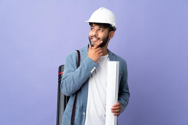 헬멧을 가진 젊은 건축가 모로코 남자와 웃고있는 동안 고립 된 찾고 청사진을 들고