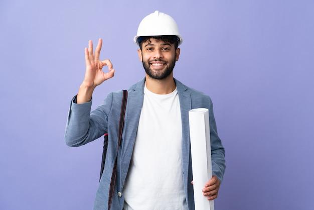 헬멧을 가진 젊은 건축가 모로코 남자와 손가락으로 확인 기호를 보여주는 고립 된 청사진을 들고