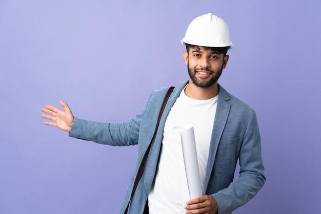 헬멧을 가진 젊은 건축가 모로코 남자와 고립 된 벽에 청사진을 들고 와서 초대하기 위해 손을 옆으로 확장