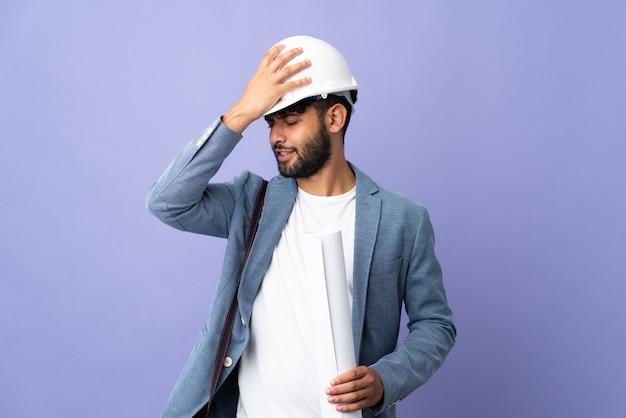 헬멧과 격리 된 벽에 청사진을 들고 젊은 건축가 모로코 남자는 뭔가를 실현하고 해결책을 계획하고 있습니다
