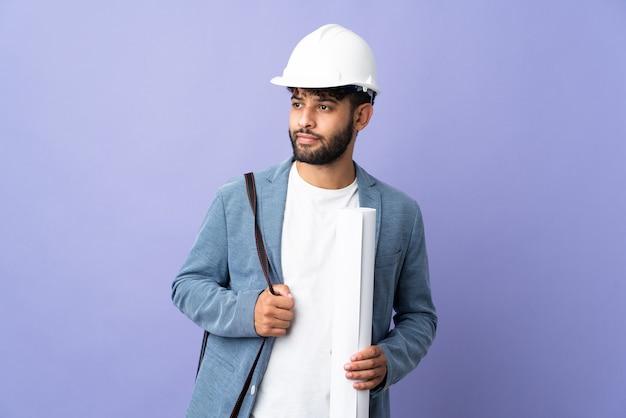 헬멧과 측면을 찾고 고립 된 벽에 청사진을 들고 젊은 건축가 모로코 남자