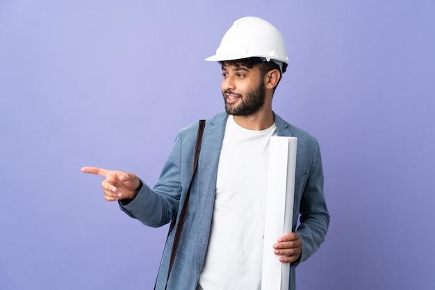 헬멧과 측면에 손가락을 가리키는 고립 된 벽에 청사진을 들고 젊은 건축가 모로코 남자
