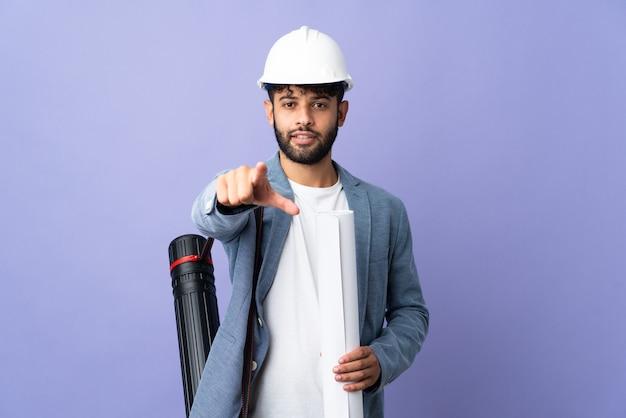 헬멧과 격리 된 벽에 청사진을 들고 젊은 건축가 모로코 남자 놀라게하고 앞을 가리키는