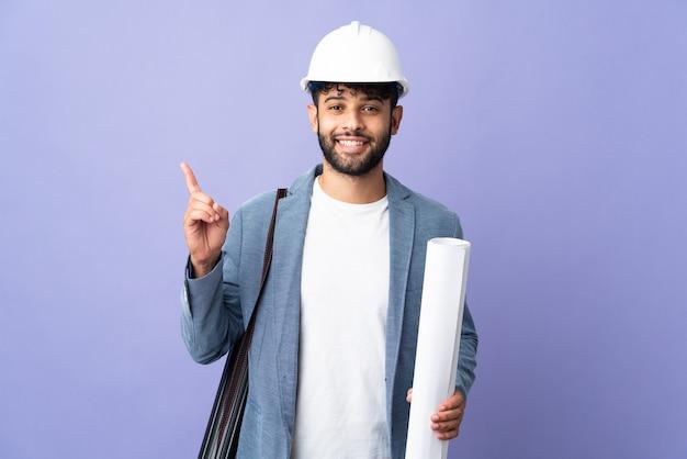 헬멧을 가진 젊은 건축가 모로코 남자와 손가락을 가리키는 아이디어를 생각 격리 된 벽에 청사진을 들고