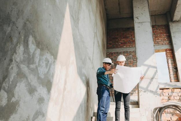 건물에서 작업이 어떻게 진행되고 있는지 그의 소유자에게 보여주는 젊은 건축가.