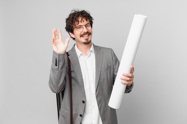 幸せに笑って、手を振って、あなたを歓迎し、挨拶する若い建築家