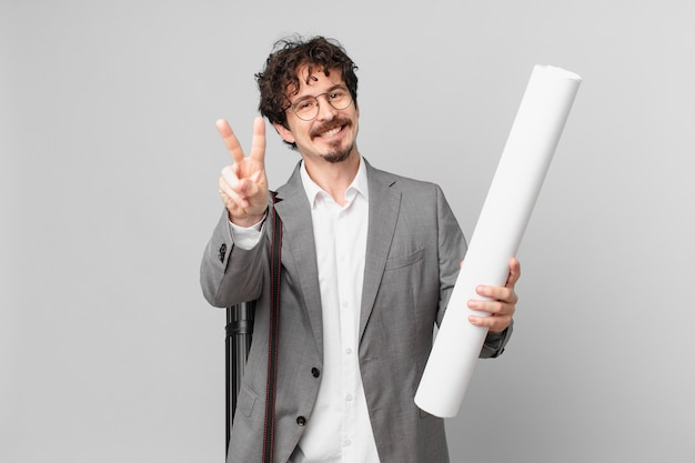 Young architect smiling and looking happy, gesturing victory or peace
