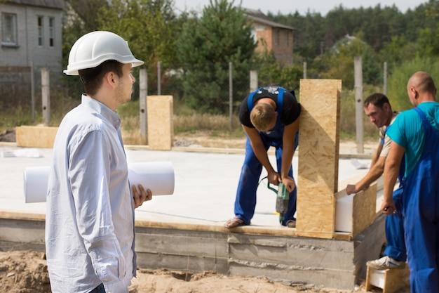 건설 현장에서 건설 노동자를 지켜보고 서 있는 그의 팔 아래에 압연된 청사진을 가진 젊은 건축가