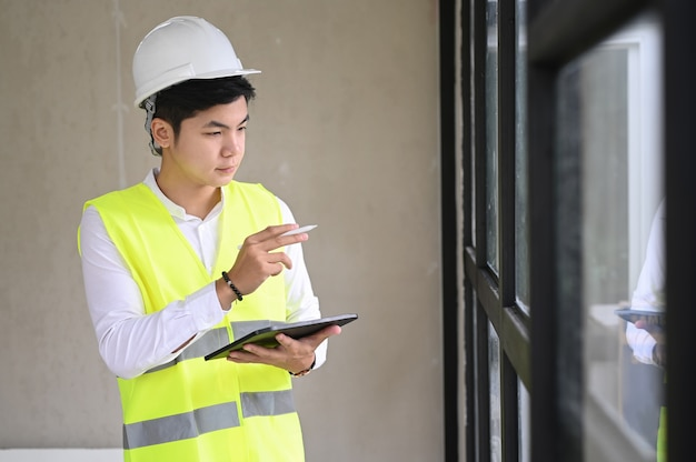 Young architect with helmet and tablet at construction site, checklist concept