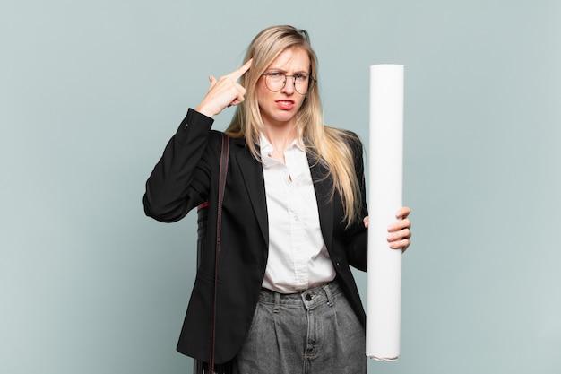 Молодая женщина-архитектор смущена и озадачена, показывая, что вы сошли с ума, сошли с ума или сошли с ума