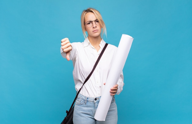 Young architect woman feeling cross, angry, annoyed, disappointed or displeased, showing thumbs down with a serious look