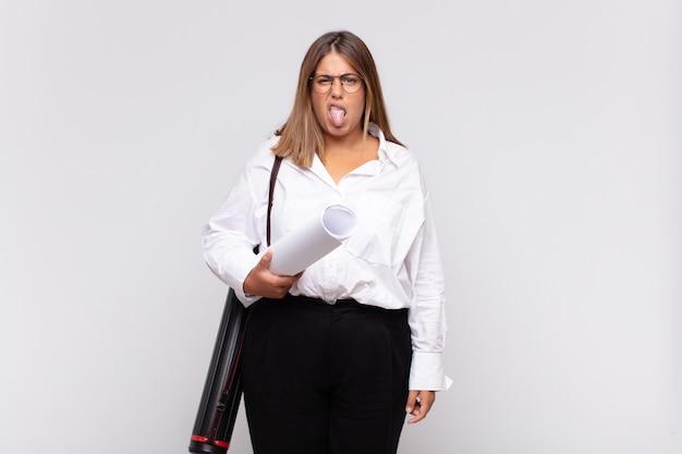 Молодая женщина-архитектор чувствует отвращение и раздражение, высунув язык, не любит что-то противное и противное