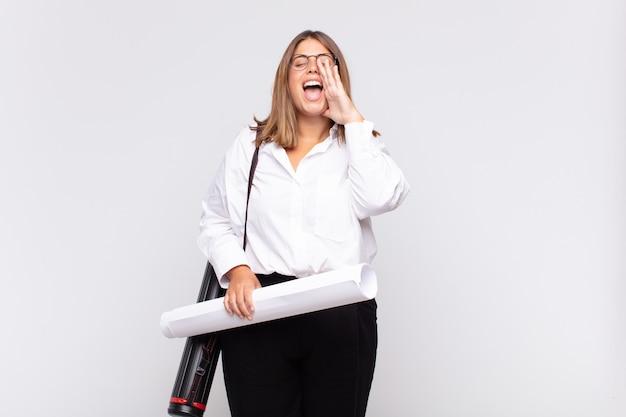 젊은 건축가 여자가 행복하고 흥분되고 긍정적 인 느낌, 입 옆에 손으로 큰 소리를 지르고 외침
