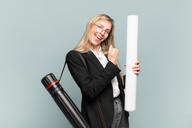 Young architect woman feeling happy, positive and successful, motivated when facing a challenge or celebrating good results