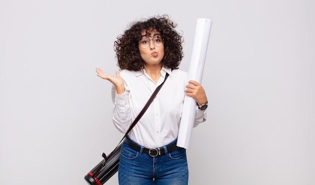 Молодая женщина-архитектор чувствует себя озадаченной и сбитой с толку, сомневаясь, взвешивая или выбирая разные варианты с забавным выражением лица