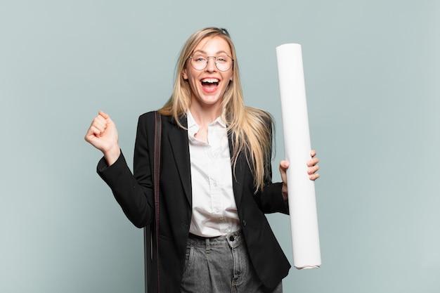 Молодая женщина-архитектор, чувствуя себя потрясенной, взволнованной и счастливой, смеясь и празднуя успех, говоря