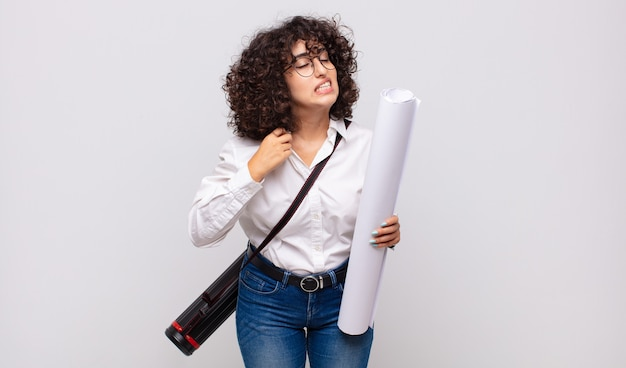 若い建築家の女性は、ストレス、不安、疲れ、欲求不満を感じ、シャツの首を引っ張って、問題で欲求不満に見える