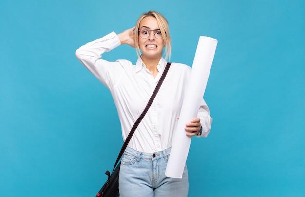 Молодая женщина-архитектор, чувствуя стресс, беспокойство, беспокойство или испуг, с руками за голову, паникует из-за ошибки