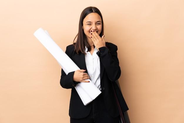 젊은 건축가 여자 청사진을 들고 행복하고 손으로 입을 덮고 웃고