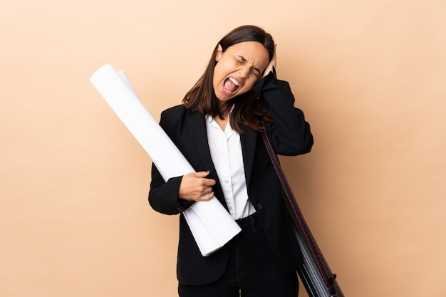 Young architect woman holding blueprints over isolated background stressed overwhelmed