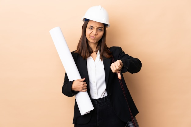 Young architect woman holding blueprints over isolated showing thumb down with negative expression