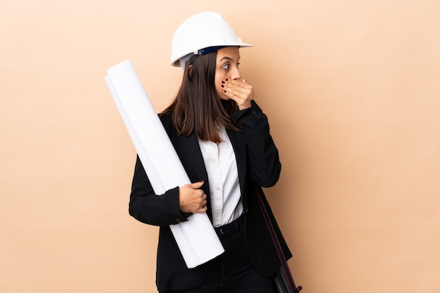 Young architect woman holding blueprints over isolated wall covering mouth and looking to the side