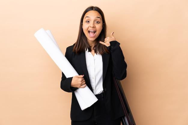 젊은 건축가 여자 전화 제스처를 만드는 격리 된 배경 위에 청사진을 들고. 나에게 다시 전화