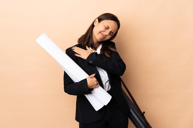 노력을 한 데 대한 어깨에 통증을 앓고 격리 된 배경 위에 청사진을 들고 젊은 건축가 여자