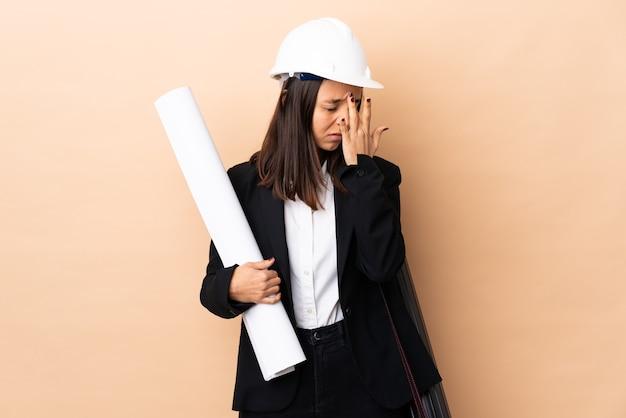 두통으로 격리 된 배경 위에 청사진을 들고 젊은 건축가 여자