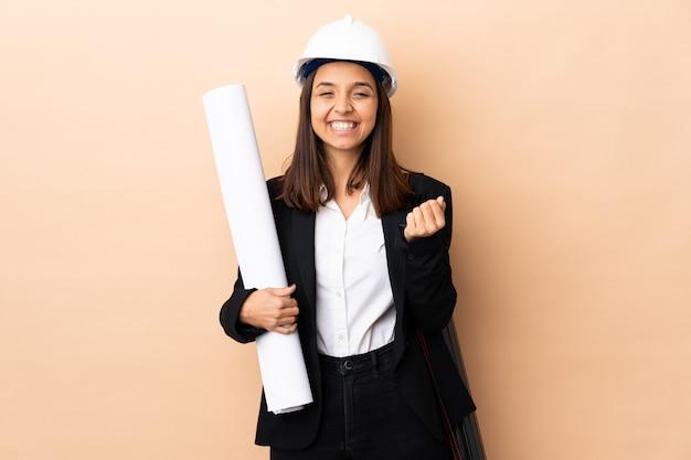 孤立した笑いに青写真を保持している若い建築家女性